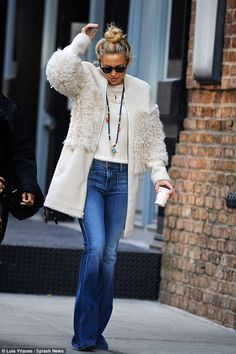 Flare for fashion: The actress wore bell-bottoms and a large woolly coat while out with designer Richard Stark
