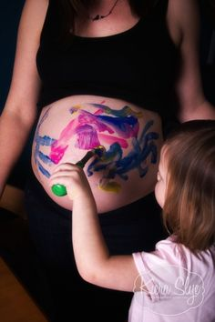 Cute Maternity photo idea. Get the siblings involved to paint a picture on the expectant mother's belly.