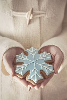 Woman holding a snowflake cookie by Sandra Cunningham