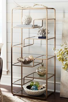 Modern asymmetrical styling, rounded corners, 10 clear glass shelves and a striking metallic gold finish all combine to make Pier 1's Enzo Tall Shelf a versatile storage solution for any space. Be careful not to overload your shelves in a small space—your accents, books or photos need space to breathe in order to avoid a cluttered look.
