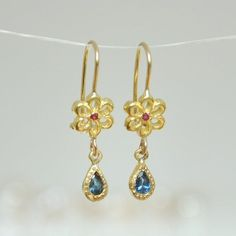 Dainty dangle 18k gold flower boho dangle earrings with beautiful blue teardrop Sapphire hanging set in 18k solid gold bezel. #earrings #sapphire #goldearrings #malkaravinajewelry