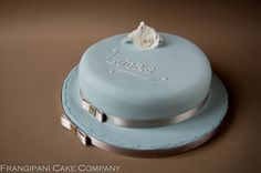 A simple cinnamon sponge cake with a butter cream filling, covered in baby blue sugar paste with white roses.