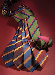 Our unique hand rolled and hemmed double warp silk neckties, solid on reverse in a color complementary to the dual stripes on face. Shown left to right: A-storm blue with saffron and claret; C-claret with saffron and midnight; D-cobalt with chili and saffron; E-rust with Stewart and saffron; G-sage with fuchsia and navy.