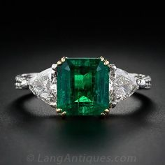 This classic trio includes a stunning rich green emerald-cut emerald weighing 2.34 carats, flanked by a pair of sparkling trillion-cut diamonds together weighing 0.80 carats. This superbly crafted handmade ring is composed of platinum with an 18K yellow gold setting for the emerald and  exquisite hand engraving throughout. A truly stunning and timeless estate emerald and diamond ring.