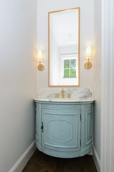"""Bathroom Blue Cabinet Paint Color. Turquoise Blue Half Moon Floating Washstand with Tall Brass Mirror. I asked the designer about the color used on this bathroom cabinet and I was very surprised with what she told me about this cabinet. What a brilliant idea! """"Actually, this is not a custom piece, this was the Tucci cabinet by SteinWorld found on Wayfair for $569.99! Since this was going in a speculative build, I wanted to maximize investment dollars. Our cabinet maker wanted to charge over…"""