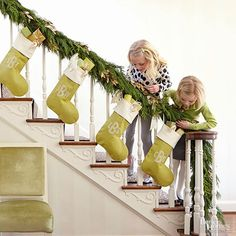 10 Simple Christmas decorating ideas to pin now and do later. (Matching stockings + garland going up staircase.) Image via BHG.