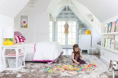 """Play On~Harper's dollhouse-like bedroom is tailor-made for a young girl. """"She loves books, so we made sure they were reachable,"""" says Lewis. """"Architecturally speaking, this room is so great; I just wanted to keep it light and bright."""" Chandelier and bedding by Serena & Lily; wallpaper by Eskayel."""
