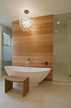 A minimalist master bathroom with a glass shower enclosure behind a natural wood wall. The wall has the mounted faucet for the soaking tub, and above it hangs a bubble chandelier, perhaps the most fitting chandelier for a bathroom.