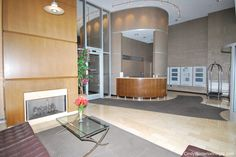Lobby with Fireplace and updated seating  travertine tile curved front desk for Doorman track lighting and glass security doors Chicago Located in the 700 Block of Wells listed by Stephanie Derderian Wood floors green couch fire place and city views