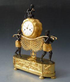 """c1815 Zeldzame Empire 'Au Bon Savage' klok, 'Jonge zwarte dragers', Godeby à Paris, circa 1815. Zeer verfijnde Empire bronssculptuur in vuurverguld en gepatineerd """" Aux jeunes porteuses noires """". De klok heeft een 8 daags uurwerk en een kast die wordt toegewezen van de bronsgieter Louis-Isidore Choiselat (1784-1853). De sculptuur toont twee blackamoors, twee jonge zwarte mannen die een katoenbaal sjouwen met daarbovenop - aan ketting bevestigd - op een muzikale aap met twee rieten stokken… Antique Watches, Antique Clocks, Cane Stick, Mantel Clocks, Native Indian, Interesting Faces, Watches For Men, Bronze, Antiques"""