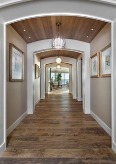 Framed Salvador Dalí originals line the entry hallway to this Gulf Coast vacation home. Wendy Berry of W Design created architectural interest with wood paneled barreled ceilings and hanging lanterns. The warm and inviting space entices you to enter and see more.