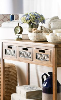 Perfect for displaying a bouquet of fresh blooms or family photographs, this weathered elm wood console table features woven accents and an open bottom shelf. Find this and more at jossandmain.com