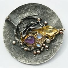 Ray Lipovsky & Eve Llyndorah: Persephone.   Pendant in sterling silver, 18k yellow gold, amethyst, blue moonstone, freshwater pearls, diamonds and leather cord.