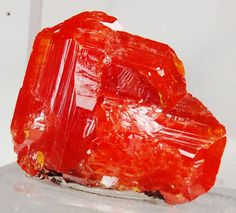 WULFENITE a lead molybdate mineral with the formula Pb Mo O 4. It can be most often found as thin tabular crystals with a bright orange-red to yellow-orange color