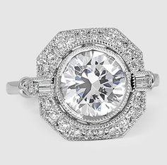 In this vintage-inspired engagement ring, a bezel-set center diamond floats above a halo of diamond accents bordered by an octagonal frame. Bezel-set baguette accents create a look of shimmering beauty.