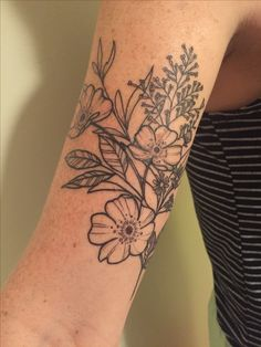 Floral wildflower arm tattoo with Wild Rose, heather aster, field thistle, and lilac.