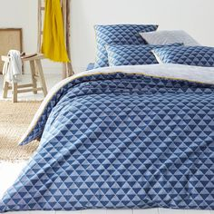 """Issor duvet cover:  In a blue graphic triangle print.                                Features of Issor duvet cover:Front printed with blue triangles; blue stripes on a white background on the back. Contrasting yellow taped edging.100% densely woven cotton (57 threads/cm²). The higher the thread count, the higher the quality of the weave.Straight edge finish.Washable at 60°.The Oeko-Tex® label guarantees that the items tested and certified do not contain any harmful substances that could be…"