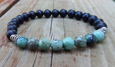 African turquoise mens beaded bracelet made with 8mm Rustic African Turquoise surrounded by smooth 8mm Matte Black Onyx. Very cool. African Turquoise Properties: Helps one to express themselves with m