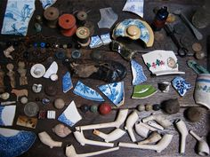 Items that John Nicolson found under the floorboards of his 18th C. house in Fournier St, including a wedding ring, pipes, buttons, coins, cotton reels, spinning tops, marbles, broken china and children's toys.