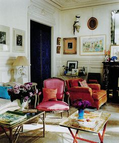 Parisian parlor, living room, filled with vintage tea trays, arm chairs, and French prints and paintings