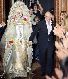 French fashion designer Christian Lacroix, right, escorting a model wearing a wedding dress. July 2009