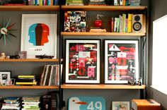 A detailed look at the well-styled bookshelf wall unit in Ty Mattson's office at SND CYN Studios, where framed artwork leans against the wall alongside books, videos, and select tchotchkes. | Interior design by Camp Design Group campdesigngroup.com sndcyn.com
