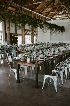 Wedding Receptions Metal chairs, draped greenery, and farmhouse tables create a industrial yet cozy feel Loft Wedding Reception, Marie's Wedding, Warehouse Wedding, Wedding Chairs, Rustic Wedding, Wedding Venues, Table Wedding, Minimalist Wedding Reception, Wedding Ideas