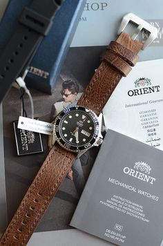 "Orient EM65008B Black Ray. Stainless steel, Japanese movement (in-house Orient Caliber 46943; non-manual, non-hacking), 40-hour reserve, screw-down crown/push, mineral crystal, uni bezel, day/date, 200m WR. MSRP US$295.00, readily available online (Amazon, etc.) for half that. (Shown with the ""Benton"" leather strap from Crown & Buckle.)"