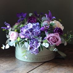 The Real Flower Company Scented Spring Rose & Anemone Purple Hat Box Arrangement is from our purple spring collection of vibrant purple flowers mixed with pastels which are inspired by the 2014 colour trends for fashion and home. This spectacular bouquet is filled with scented spring roses, hydrangeas, clematis, tulips, anemones and lavender combined with herbs and foliage. Glorious.