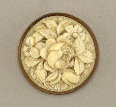 A beautiful 19th century carved ivory button. A large, carved rose and unopened buds surrounded by various other florals and leaves. Mounted in a metal collet.