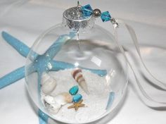 This+is+a+beautiful+Beach+glass+ornament.+It+has+decorative+white+sand+and+lots+of+various+sea+shells,+a+starfish,+tiny+sand+dollar.+Topped+off+with+matching+beads+and+ribbon.