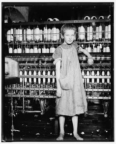 """This image features 12-year-old Addie Card, a spinner in a North Pownal Cotton Mill. Other young girls in mill told photographer Lewis Hine that she was ten years, but Hine reports that """"she admitted to me she was twelve."""" She started work as a spinner during school vacation but told Hine she would stay, February 1910.  Photo credit: Lewis Hine"""