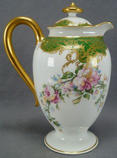 Decorated with large pink and white roses and small blue flowers. With gold gilt scrollwork and lattice designs over green at the top. Gold gilding to the handle and finial. Porcelain Ceramics, China Porcelain, Green Garland, China Tea Sets, Antique China, Antique Dishes, Coffee Set, Chocolate Pots, Kakao