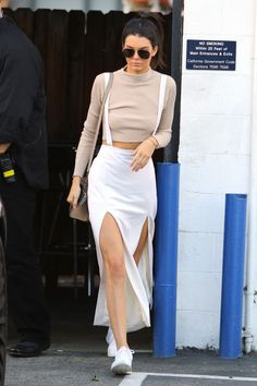 Kendall Jenner in LA wearing a white skirt and suspenders, a cropped sweater and aviator sunglasses.
