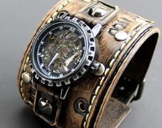 Mens two tone brown color watch cuff made with veg tanned leather, completely handmade, hand tooled, hand stitched with natural thread. The leather cuff is 2 1/2 inches wide. Item includes mechanical golden watch face what is removable and interchangeable. High quality heavy duty buckle provides closure.  THIS WATCH IS MADE TO ORDER, please use the following measuring technique to determine your wrist size and leave a note at checkout or a message.  Measure your wrist over and around the...