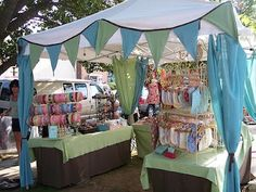 craft booth design idea-like the curtains and flags to jazz up the tent.