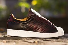 adidas Originals is currently shipping an edition of the Superstar in a very rustic look. Leather built, the kicks are set in burgundy with a color imp Adidas Shoes, Adidas Men, Sneaker Magazine, Red Sneakers, Adidas Superstar, Shoe Brands, Fashion Shoes, Men Fashion, Adidas Originals