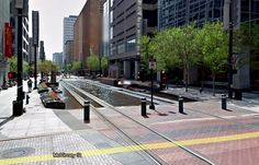 forget grass track beds, how about water?    Grass track beds can make light rail systems a lot prettier, and so a lot of places use them. But check out this bit of creative thinking out of Houston, where they use water: