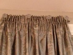 Curtains mounted with glass kitchen knobs.