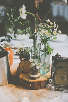 Wooden Slabs Topped with Glass Bottles & Flowers Stems as Table Centrepieces | DIY Rustic Wedding at Shustoke Farm Barns in Warwickshire | Images by James Melia | http://www.rockmywedding.co.uk/jo-lee/