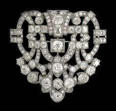 A diamond clip, circa 1930. The scrolling openwork cartouche set with cushion-shaped, old brilliant and single-cut diamonds, diamonds approximately 17.95 carats total, length 5.5cm