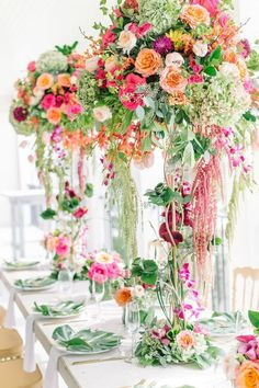 These centerpieces are oh-so-beautiful! The bold colors and tall vases are simply gorgeous.