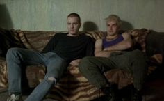 Two of the man characters sitting on a worn-out couch