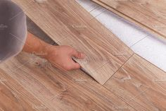 Installing laminate flooring. Carpenter lining parquet boards to by Anna Moskvina on @creativemarket