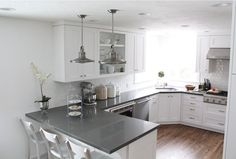 White with gray countertops. Shaker cabinets. These go to the ceiling but with no molding at the top. Although I like a bit of molding at the cabinet ceiling junction, I really like this too. It looks a bit more modern.