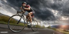 A low angle view of a professional male cyclist riding on a flat deserted road through mountainous terrain under a dark and stormy evening sky at sunset. The cyclist is wearing generic cycling suit,...