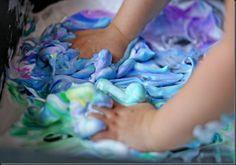 Verven met scheerschuim en waterverf. Je doet het samen in een grote kom en de baby's kunnen er met hun handen in roeren en kneden zodat de kleuren kunnen mengen. Het is een erg leuk gevoel voor de kindjes hun handjes