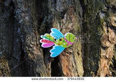 Beautiful wooden colored buttons in the shape of a bird on a wooden background, wooden bark.Place for text.
