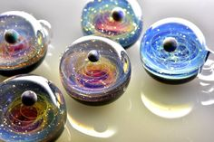 Glass artist Satoshi Tomizu sculpts small glass spheres that appear to contain entire solar systems and galaxies. Planets made of opals, flecks of real gold, and trails of colored glass Resin Crafts, Resin Art, Glass Jewelry, Glass Beads, Jewellery, Glass Paperweights, Japanese Artists, Solar System, Glass Pendants