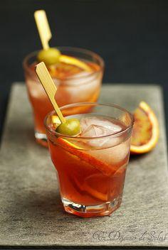 Cocktail Spritz (pour 2 personnes)   - 15 cl de Campari ou d'Apérol *  - 15 cl de Prosecco ou de Spumante  - 15 cl d'eau pétillante (eau de Seltz)  - 4 olives vertes dénoyautées  - 2 à 4 tranches d'orange ou de citron (non traités)  - 4 glaçons